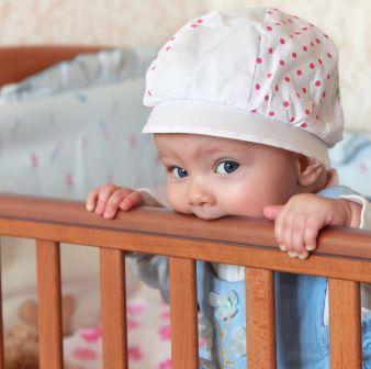 ребенок в стоит в кроватке